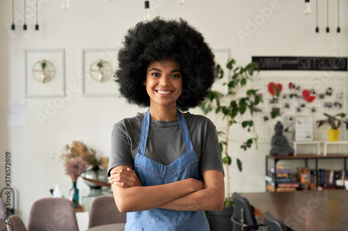 Canvastavla Happy African American young woman with Afro hair modern cafe small business owner, female waitress in reopened restaurant looking at camera standing arms crossed in cozy cafe interior