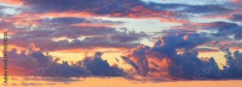 Obraz Epic dark sunset sky above the sea shore after the storm. Dramatic glowing colorful red clouds, natural texture, background. Fickle weather, climate change, ecology. Panoramic view - fototapety do salonu