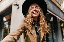 Cute Blonde In A Hat And A Fashionable Scarf Around Her Neck Makes A Selfie. Portrait Of A Girl With Burning Cheerful Eyes And An Amazing Smile.