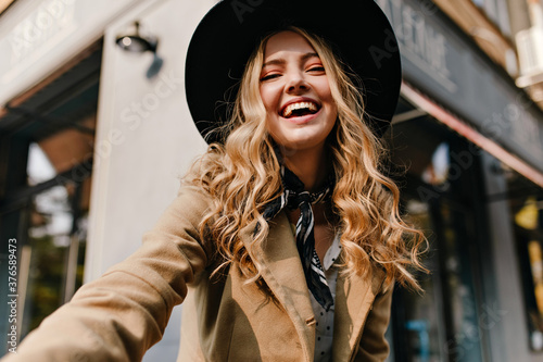 Obraz na plátně Cute blonde in a hat and a fashionable scarf around her neck makes a selfie