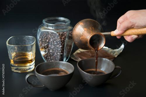 Two dark cups of coffee on a black background Fototapeta
