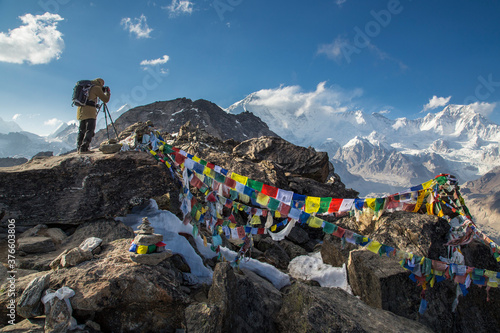 Photo A photographer with a backpack stands on top of a mountain and shots the mountains around