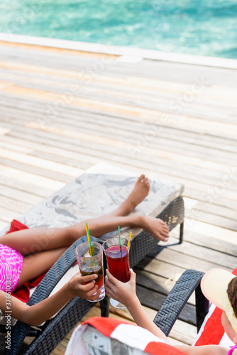 high angle view of girls sitting in sunbeds and clinking glasses with fresh cock Fototapet