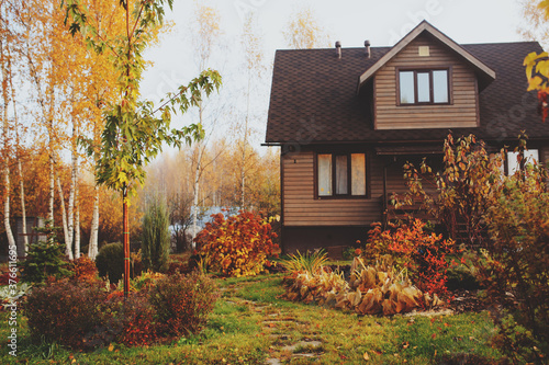 Vászonkép autumn wooden country house and garden view