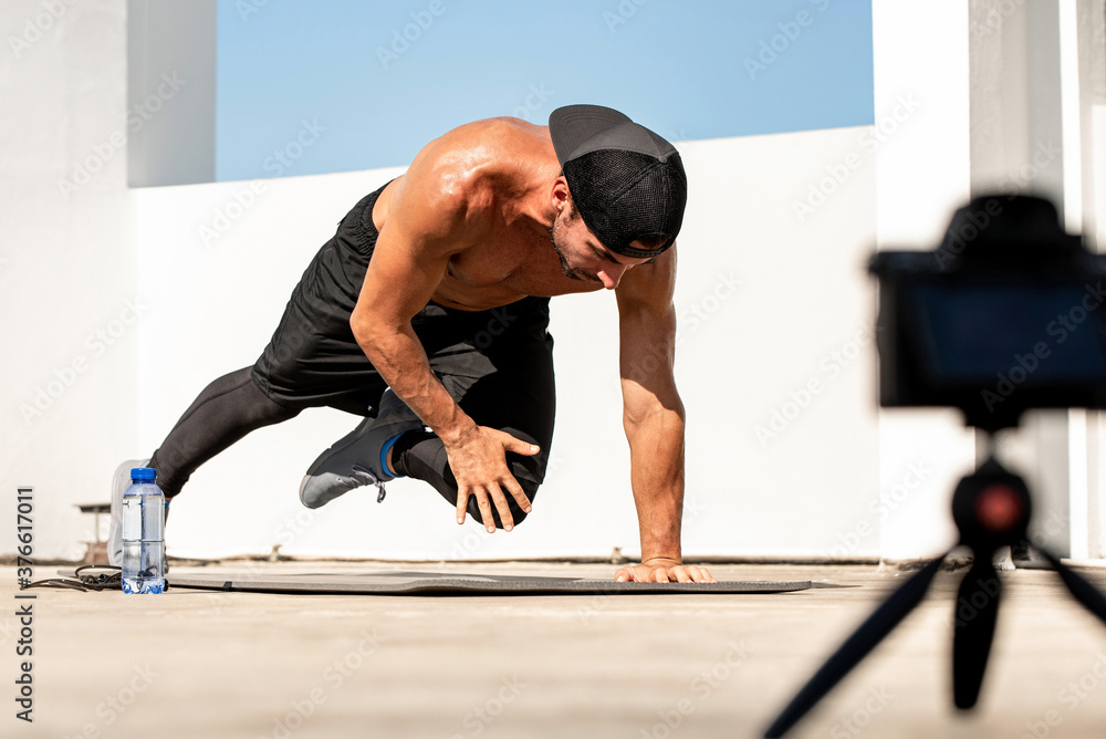 Fototapeta Male fitness influencer recording ourdoor home exercise video clip with camera on rooftop