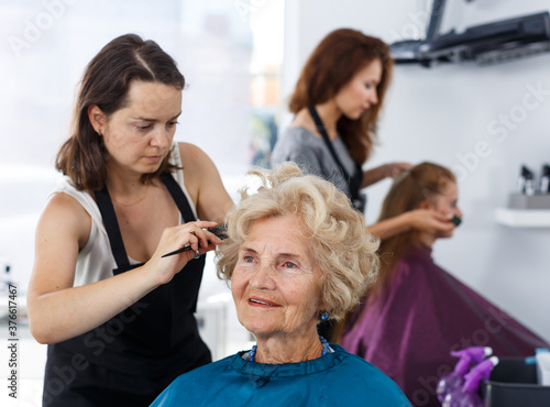 Skilled woman hairdresser making hairstyle for elderly female client in hair studio Wallpaper Mural