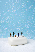 Miniature People On The White Soap Working On Snow. Minimal Winter Activity Concept. Flat Lay.