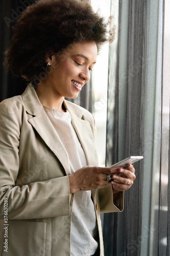 Portrait of a successful business woman using phone in office - 376630289