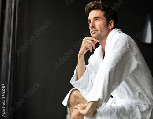 Fotografija Young, handsome man in the morning thinking while sitting in a hotel room in a r