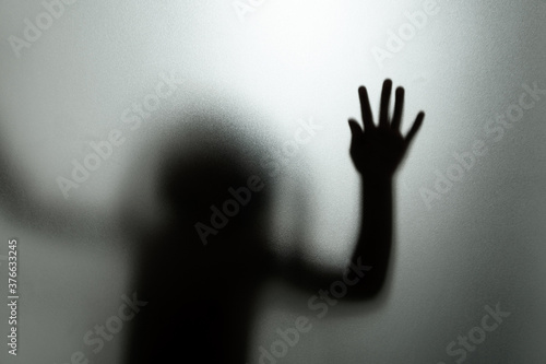 Fotografiet Ghost concept shadow of a child behind the matte glass blurry hand and body soft