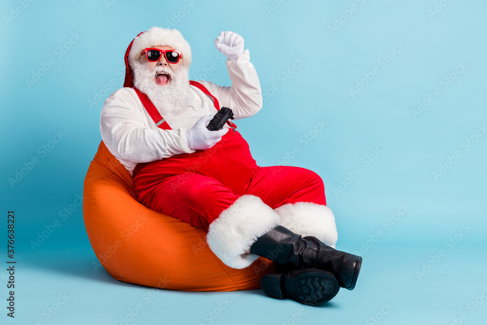 Fototapeta Full length photo of retired old man grey beard joystick crazy win playstation against boss sit beanbag wear red santa x-mas costume suspender sunglass cap isolated blue color background