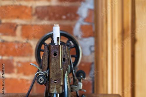 Fragment starej maszyny do szycia z nicią, na tle ceglanej ściany.