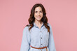 Smiling charming beautiful attractive pretty young brunette woman 20s wearing casual blue shirt dress posing standing looking camera isolated on pastel pink colour background, studio portrait.
