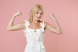 Smiling strong beautiful attractive young blonde woman wearing white summer dress spreading hands showing biceps muscles looking camera isolated on pastel pink colour background, studio portrait.
