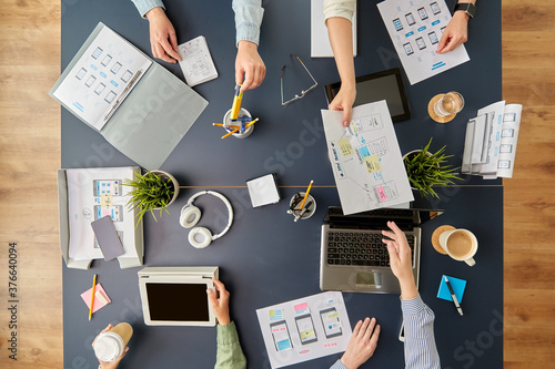 business, people and team work concept - team of startuppers with gadgets and papers working at office table
