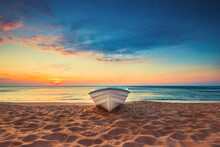 Tropical Seascape With A Boat On Sandy Beach At Cloudy Sunrise Or Sunset