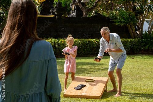 Canvastavla Happy family playing cornhole game outdoor on sunny summer day
