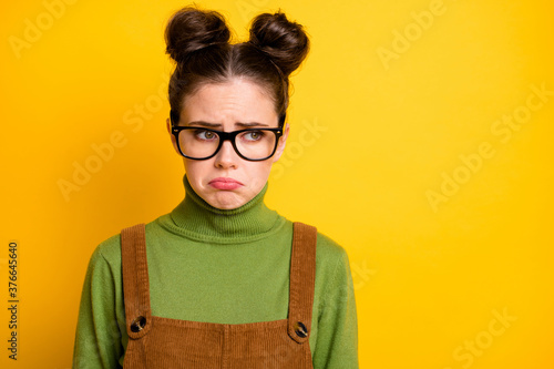 Fototapeta Photo of sad offended lady two funny buns geek nerd student failed examination crying unhappy tears grimacing wear specs green pullover brown overall isolated yellow color background obraz