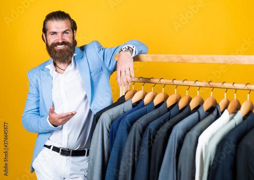 Fotografija stylish mens clothing on hanger stand in room