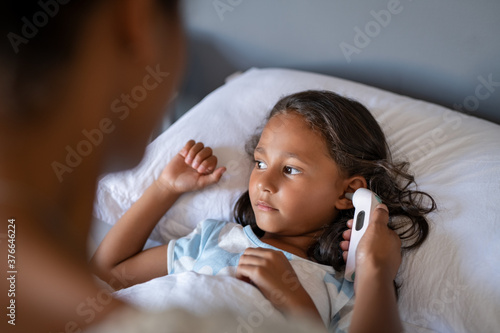 Photo Mother checking daughter temperature with ear thermometer
