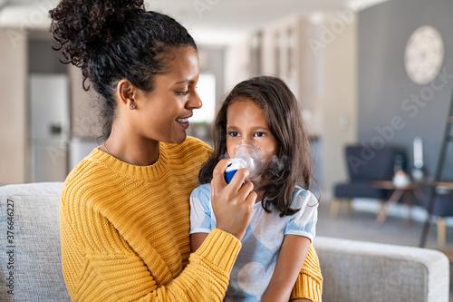 Papel de parede African mother helping child use nebulizer aerosol