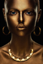 Portrait Of A Beautiful Sexy Blonde Girl With Correct Facial Features Artfully Covered With Gold Paint