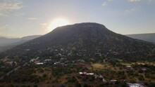 Aerial Of Morning Sunrise Coming Over Mountain Rock In Sedona, Arizona, Sun Rays Shinning Through Landscape