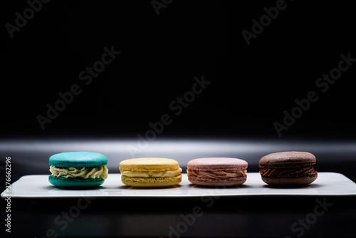 Fototapeta Macaroons of different flavors set on a dark background for a restaurant menu