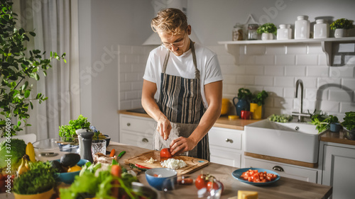 Tablou Canvas Handsome Man in White Shirt and Apron is Making a Healthy Organic Salad Meal in a Modern Sunny Kitchen