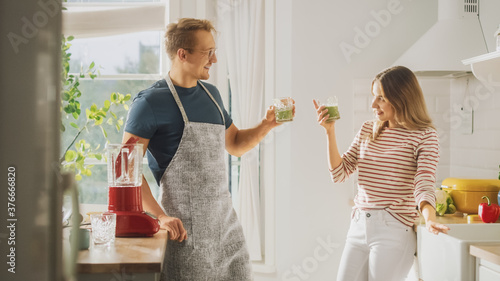 Fotografie, Tablou Handsome Young Man in Glasses Wearing Apron and Beautiful Girl are Making A Smoothie in the Kitchen