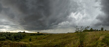 Summer Panoramic Landscape With Ominous Clouds In Overcast Sky Over The Valley Wih Hills And Fields.