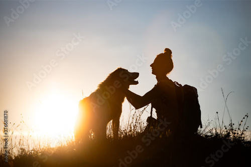 Fotografie, Obraz Woman with her dog sitting on the hill in the sunset.