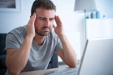 Man Feeling Migraine Seated In Front Of His Laptop