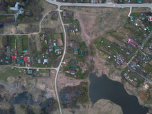 Drone Top View Of The Village At Summer Season. Roofs Of The Houses And Farms With Green Grass And Trees Surrounded By Forest. Bird's-eye View Of Roads And Pond In Settlement. Moscow Region, Russia.