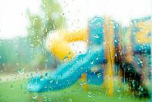 Rainy Days Rain Drops On Playground Slide In Kindergarten School.Rainy Season, Rainy Day In School.Environment, Climate Change, Season, Weathere, School In Rain Day Concept.