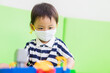 Asian toddler boy playing toy in kids club at hotel.3.5 years old boy child wearing face mask in Day care.Covid-19 coronavirus.Stay home.Social distancing in school.Back to school.New normal behavior.