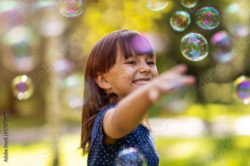 Fototapeta Girl playing with soap bubbles outdoors