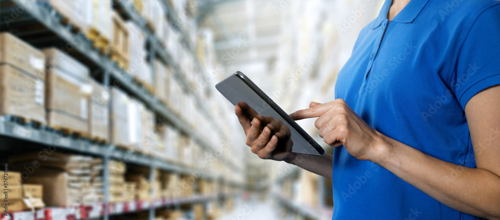 Fototapeta logistics service, warehouse management and inventory concept - female worker using digital tablet in warehouse. copy space