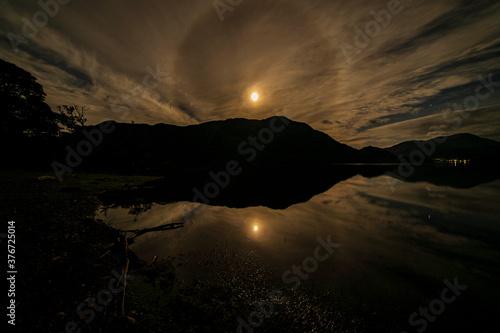 Fényképezés A Moon halo over Ullswater on a cloudy night