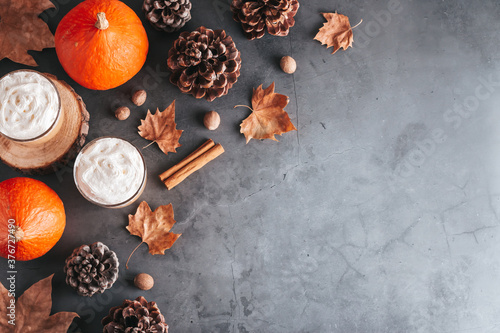 Fototapeta Autumn border with natural pine cones, pumpkins, dried leaves and pumpkin latte on dark grey stone top, top view, copy space