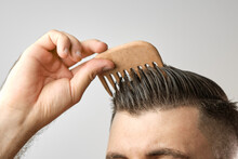 Close Up Man Brushing His Hair With Wooden Comb On The Grey Background. Treatment Against Hair Lost And Dandruff Concept. Cosmetic Products For Men. Barbershop Advertising.