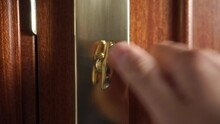The Hand Turns And Unlocks The Bronze Gold Door Bolt Lock And Opens The Door. Close-up. Selective Focus