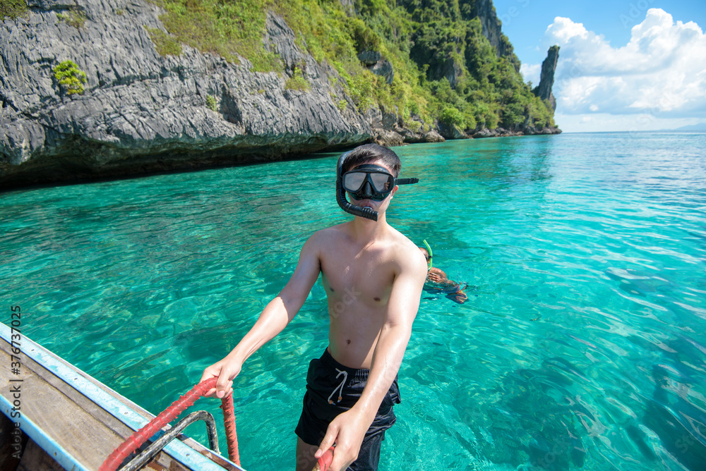 Fototapeta An active man on thai traditional longtail Boat is ready to snorkel and dive, Phi phi Islands, Thailand