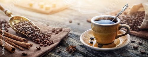 Fototapeta A cup of aromatic black coffee and coffee beans on the table. Morning Coffee Espresso for breakfast in a beautiful blue cup. obraz