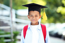 Young African American School Boy With Backpack And Graduation Cap On The Street