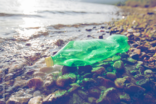 Plastic bottle waste on rivershore , water pollution concept