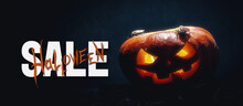 Background In The Style Of Halloween. Inflatable Balloons Of Black White And Orange Colors In Hand On A Dark Background. On The Balls Are Painted Ghosts And A Pumpkin Head.