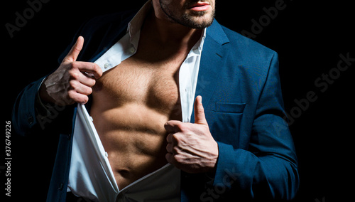 Fashionable young man wearing suit posing over black background. Handsome man posing in white shirt and dark blue suit. Sexy naked torso, six pack abs with open shirt.