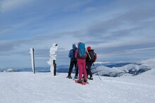 Beautiful Winter Mountain Views During A Snowshoe Hike Along The Red Ridge Trail In The Low Tatras, Slovakia - Sihouettes Of Tourists And Frozen Tourist Signpost At Velka Chochula Peak