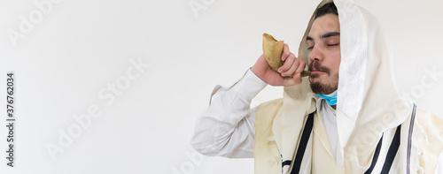 Fotografia Orthodox Jewish man blast in Shofar, ram's horn, at Rosh Hashana holiday, jewish new year